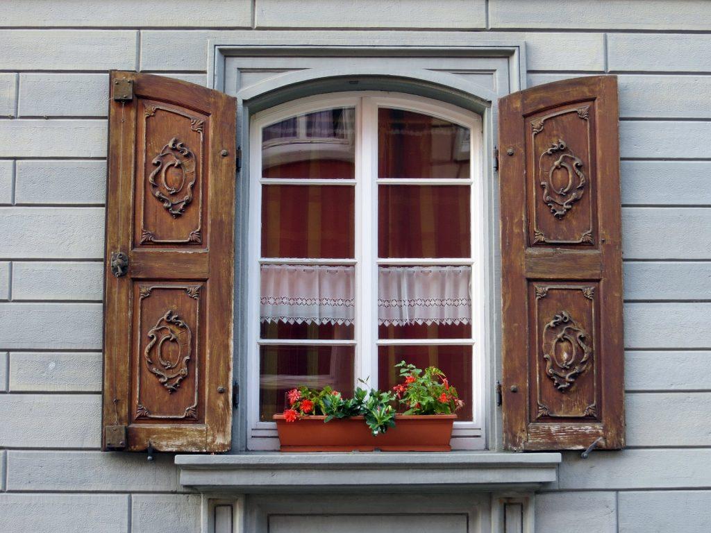 Klassiska träfönster med spröjs och dekorativa fönsterluckor av trä.