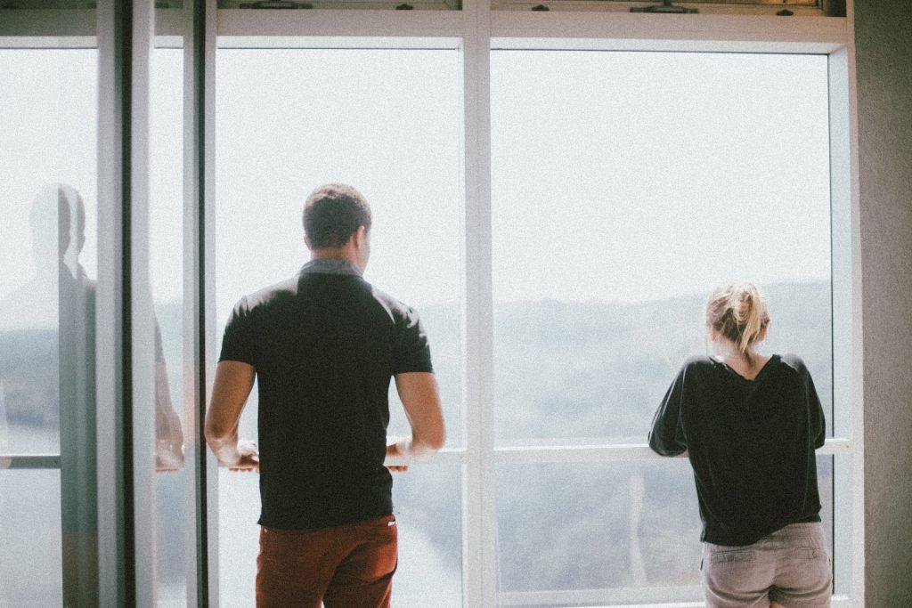 Två personer står och tittar ut från en inbyggd balkong.